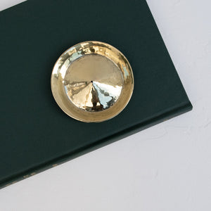 A round brass incense holder on a green book.
