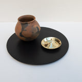 A brass incense holder on a stoneware serving platter alongside a Pai Pai short ceramic vase.