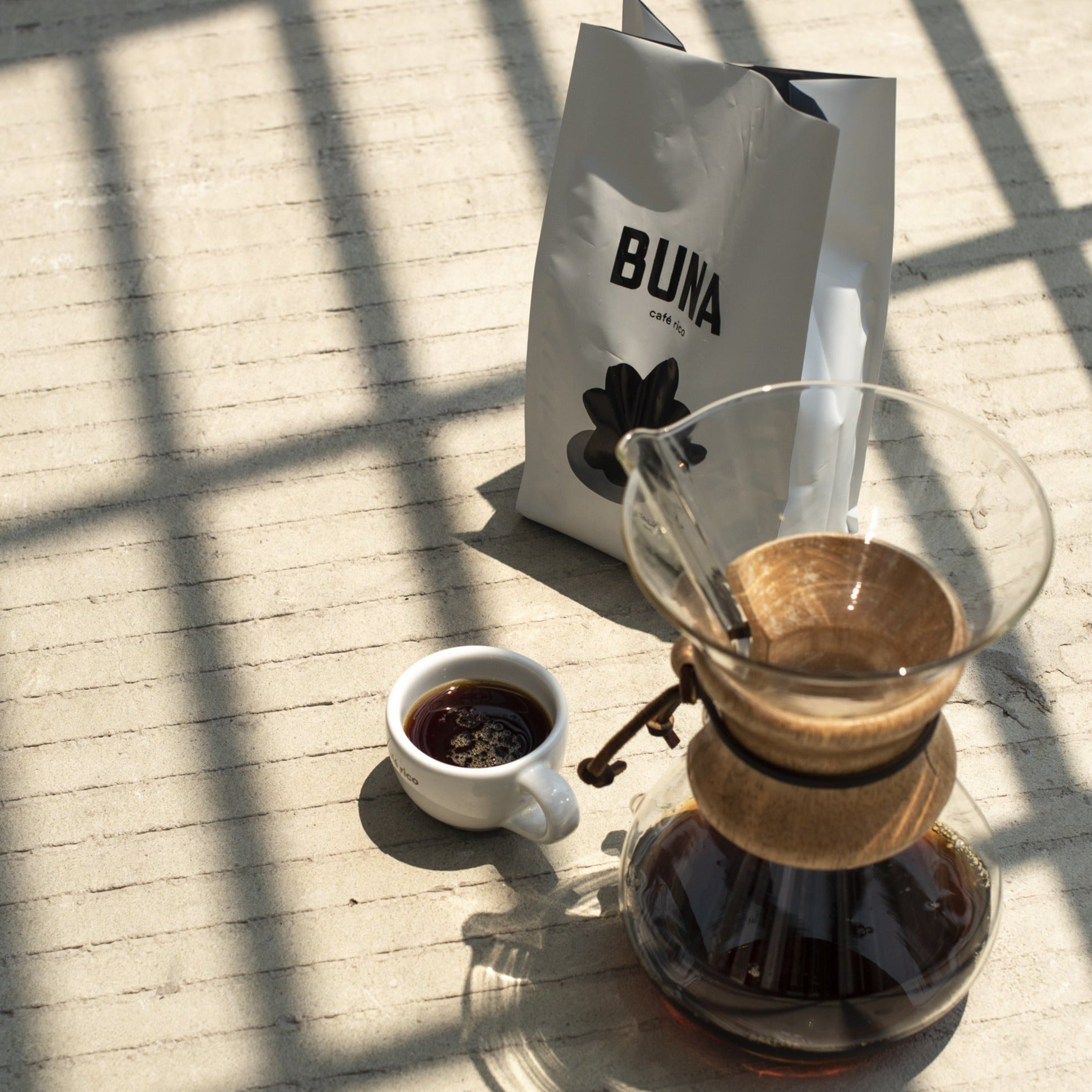 A bag of Buna coffee alongside a carafe and mug of brewed coffee.