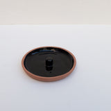 A black and terracotta ceramic incense holder.