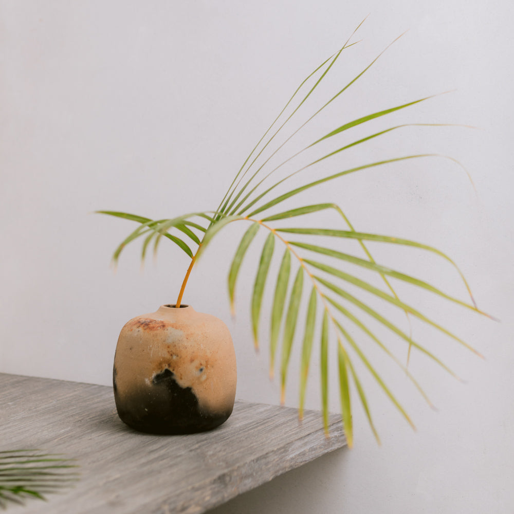 A medium cilindro vase on a shelf with a palm frond.