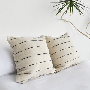 A pair of handwoven wool throw pillows on a bed with all white bedding.