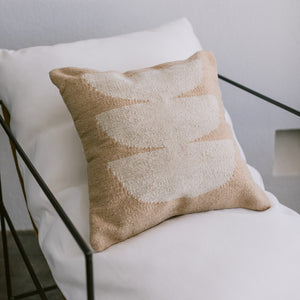 A wool ivory and beige-colored throw pillow on a white chair.
