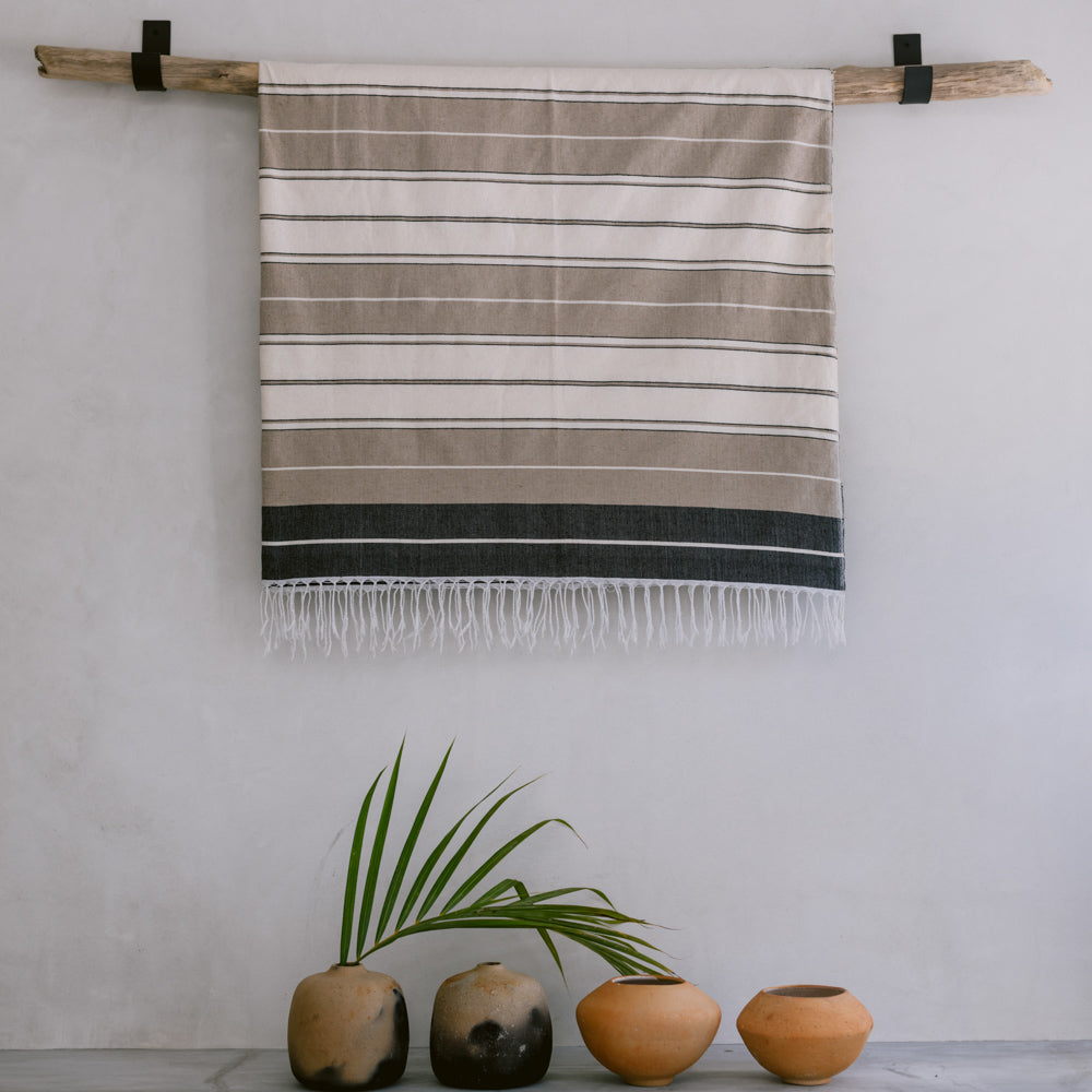 A cotton throw folded and hung on a wall hanger with ceramic vases on the floor below.