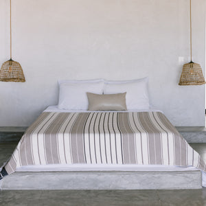 A cotton coverlet draped over a bed.