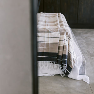 A desert stripes cotton coverlet draped over the foot of a bed.