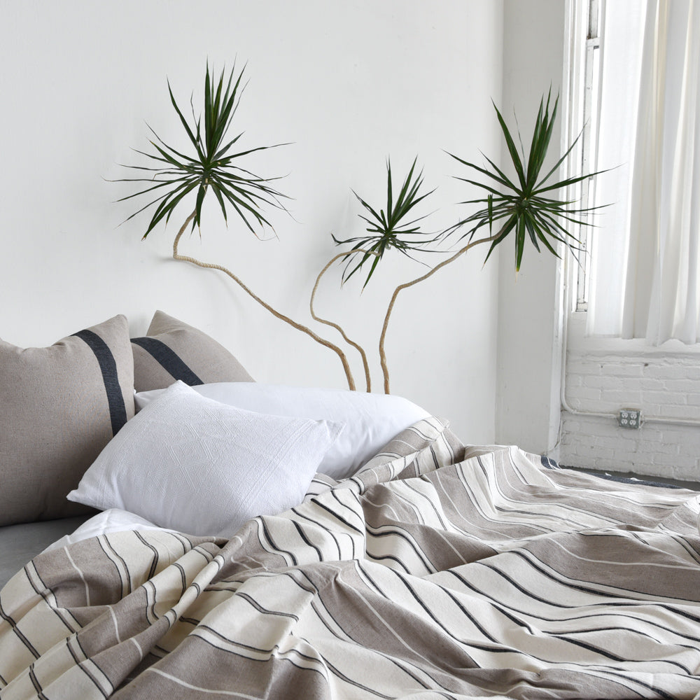 A cozy cotton coverlet blanket casually thrown on a cozy bed.