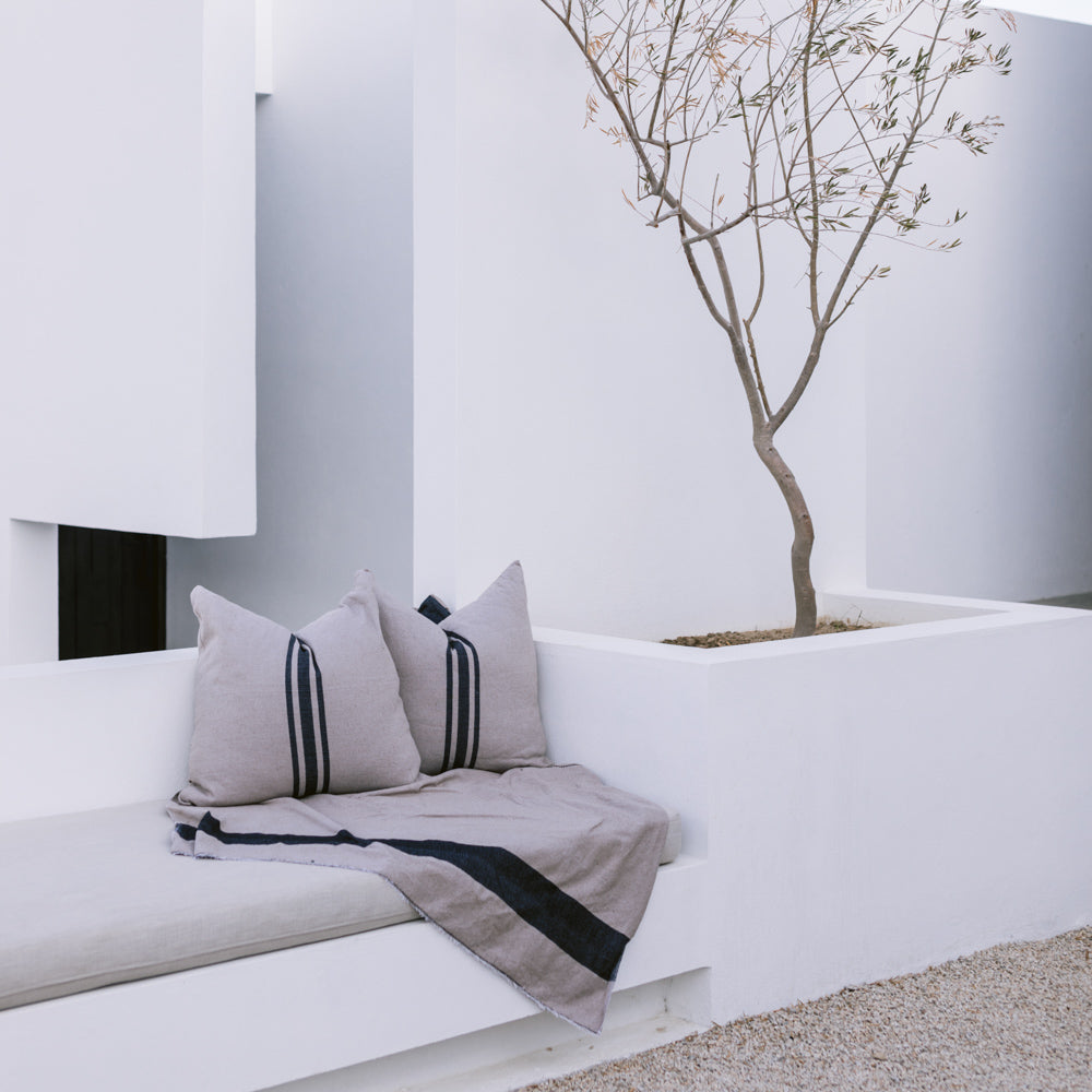 An ecru-colored cotton throw draped over a white couch with matching throw pillows.