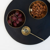 A kitchenware set up including brass serving bowls, a brass tablespoon and a black stoneware serving platter.