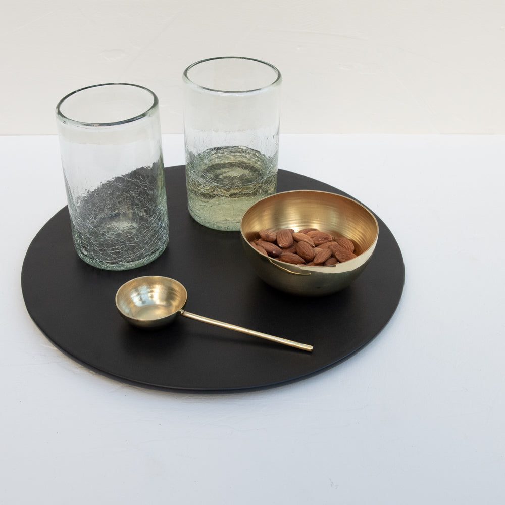 A black serving platter, small brass bowl, brass tablespoon and a set of handblown glasses.