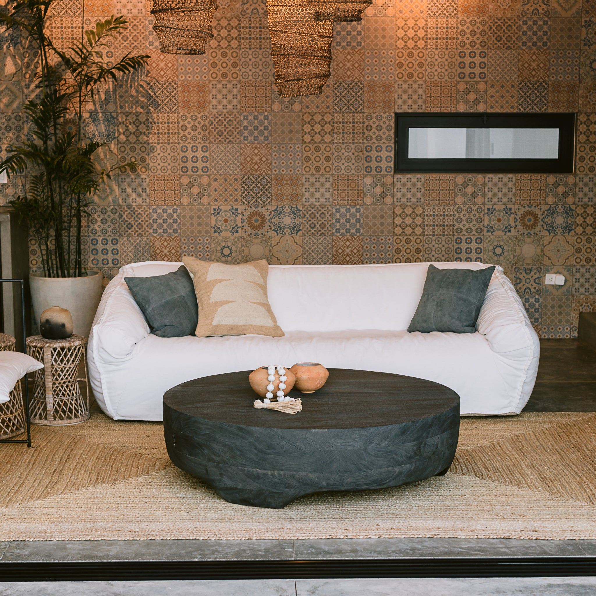 A living room featuring a white stuffed couch, wool and leather throw pillows, a modern grey coffee table and Mexican ceramics.