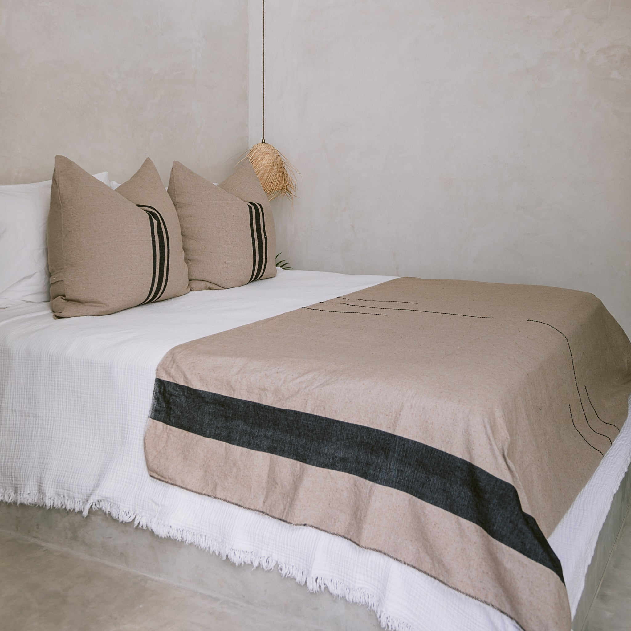 A bed neatly made with white sheets, an ecru-colored coverlet, and a pair of euro shams in matching ecru color.