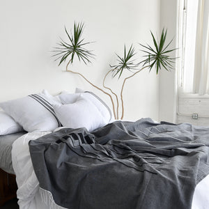 A bed made with a gray handwoven cotton throw blanket, cotton euro sham pillows and a white throw pillow. A tall yucca plant stands alongside.