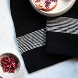 Black cotton hand towel with white stripes on a white marble counter with pomegranates in white bowls.