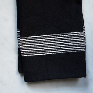 A black cotton hand towel with white stripes on a marble counter.