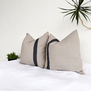 Cotton euro shams in ecru with an off-center gray stripe on a white bed.