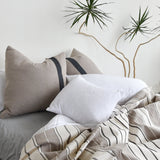 A cozy, unmade bed featuring cotton ecru-colored euro shams, white pillows, and a cotton throw blanket on a bed next next to a tall yucca plant.