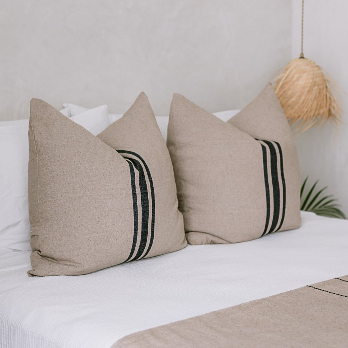 A set of cotton euro shams on a white bed with palm leaf pendant lights.