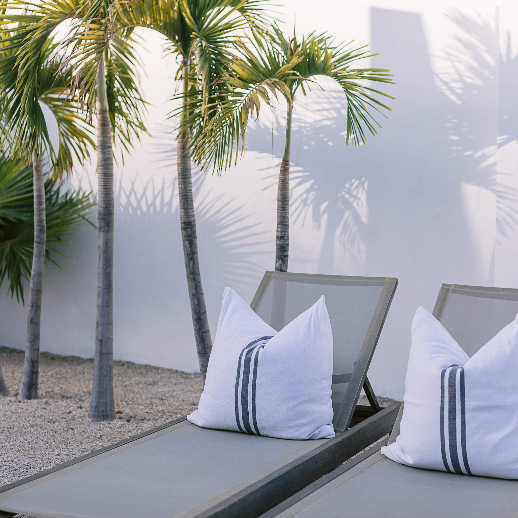 Lounge chairs with white extra-large throw pillows are next to palm trees.
