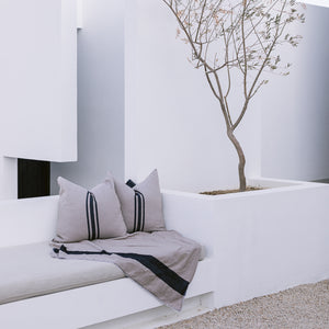 A collection of cotton textiles, including euro sham throw pillows and a cotton blanket on an outdoor couch.