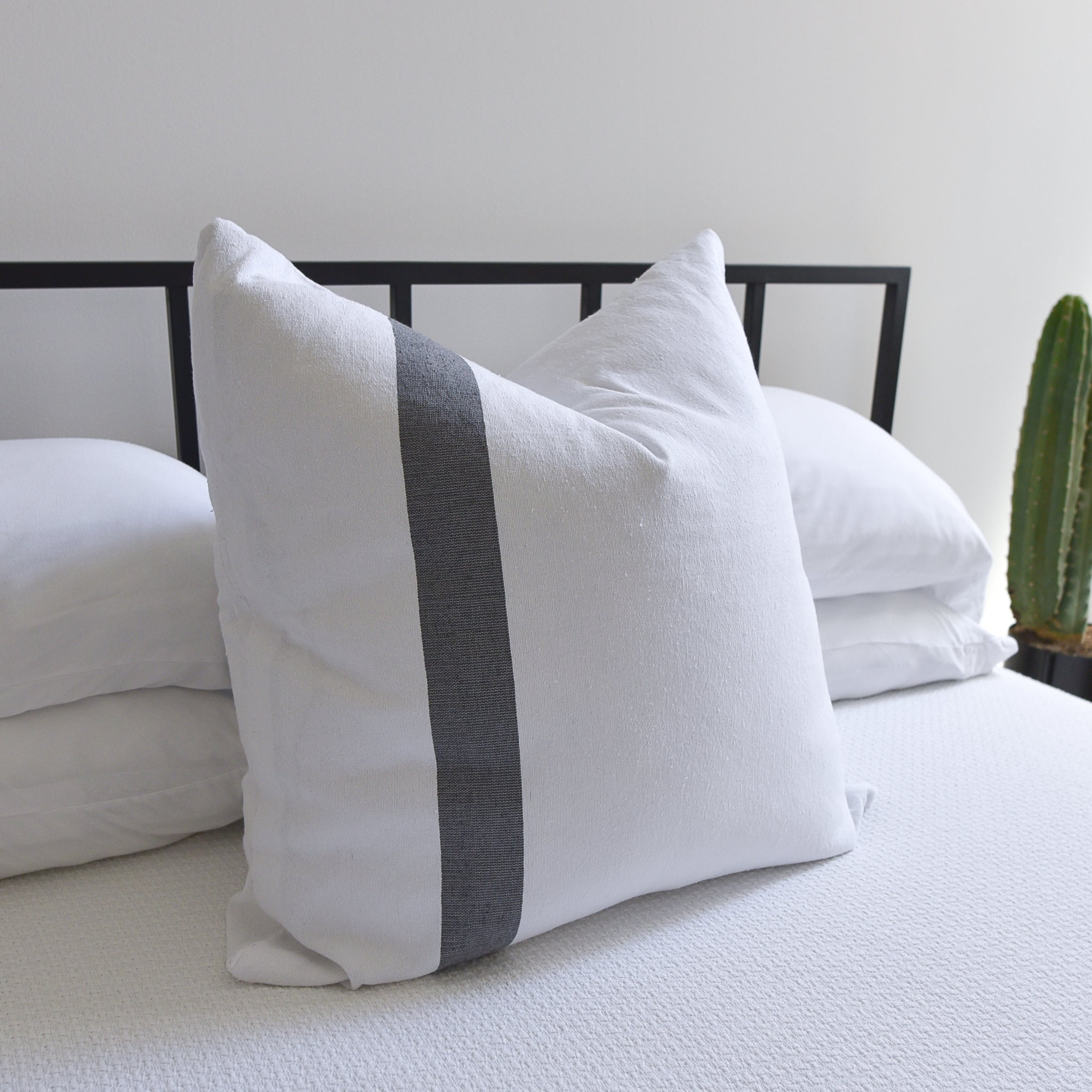 A white cotton euro sham on a bed with white bedding.