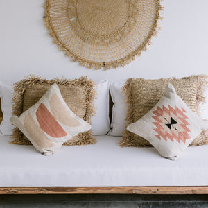 A set of wool throw pillows handwoven in Oaxaca rest againt palm throw pillows on a white couch.
