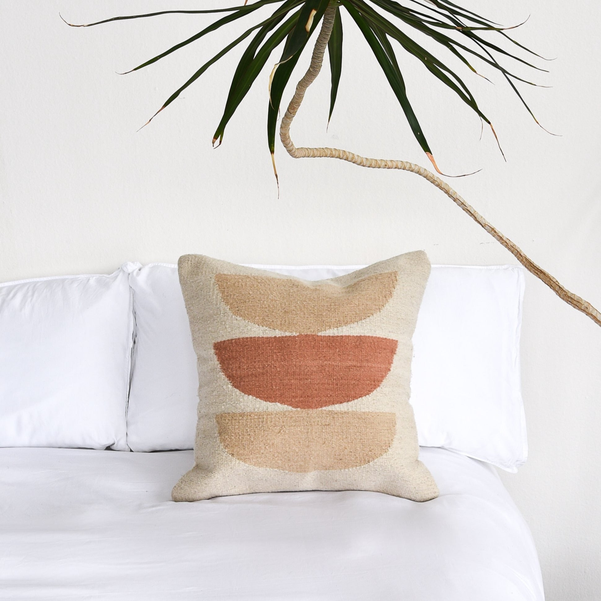 A handwoven wool pillow on a white bed with a yucca plant alongside.
