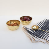 A set of small brass bowls holding grapes and almonds, along with a brass tablespoon and Oaxaca cotton hand towel.