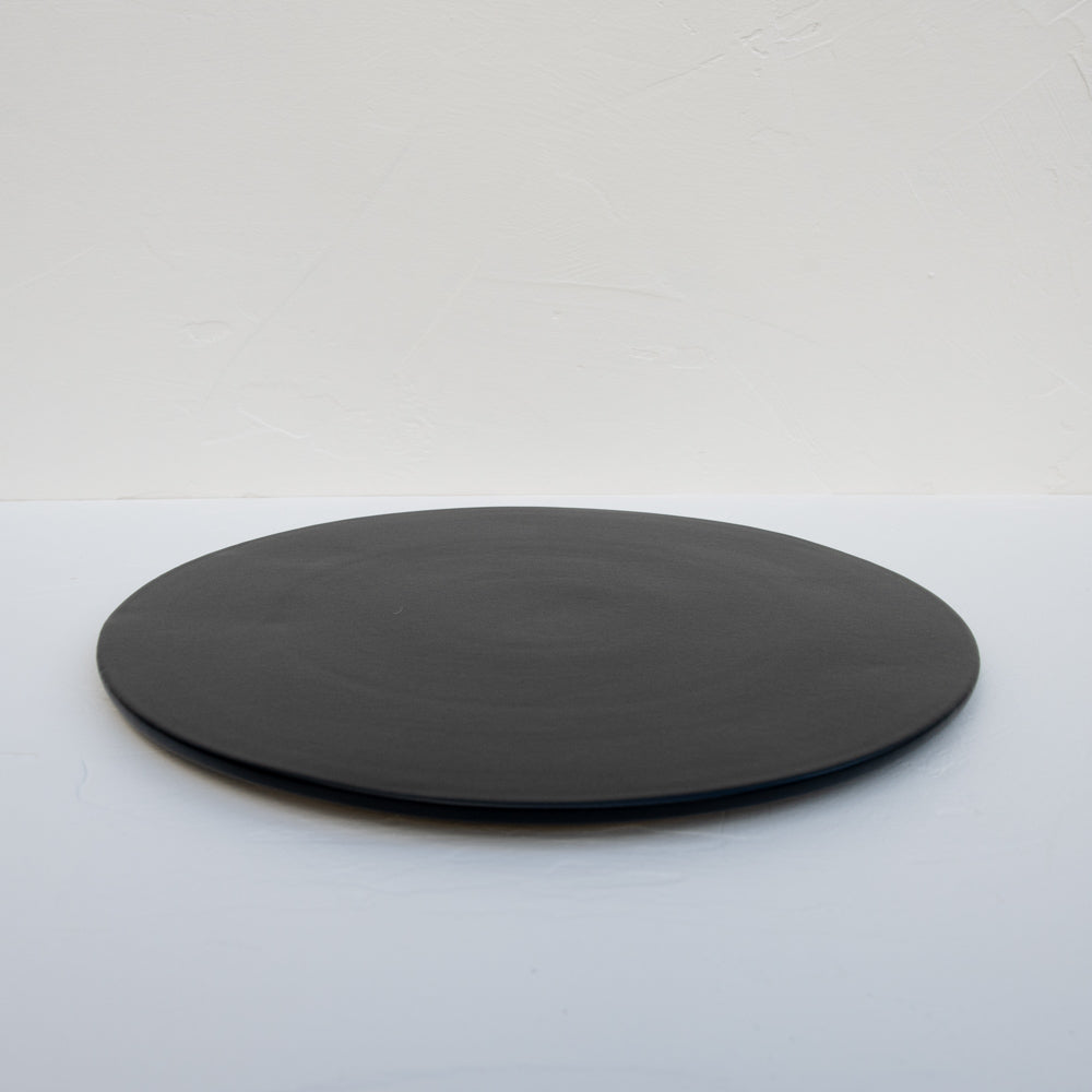 A matte-black stoneware serving platter.