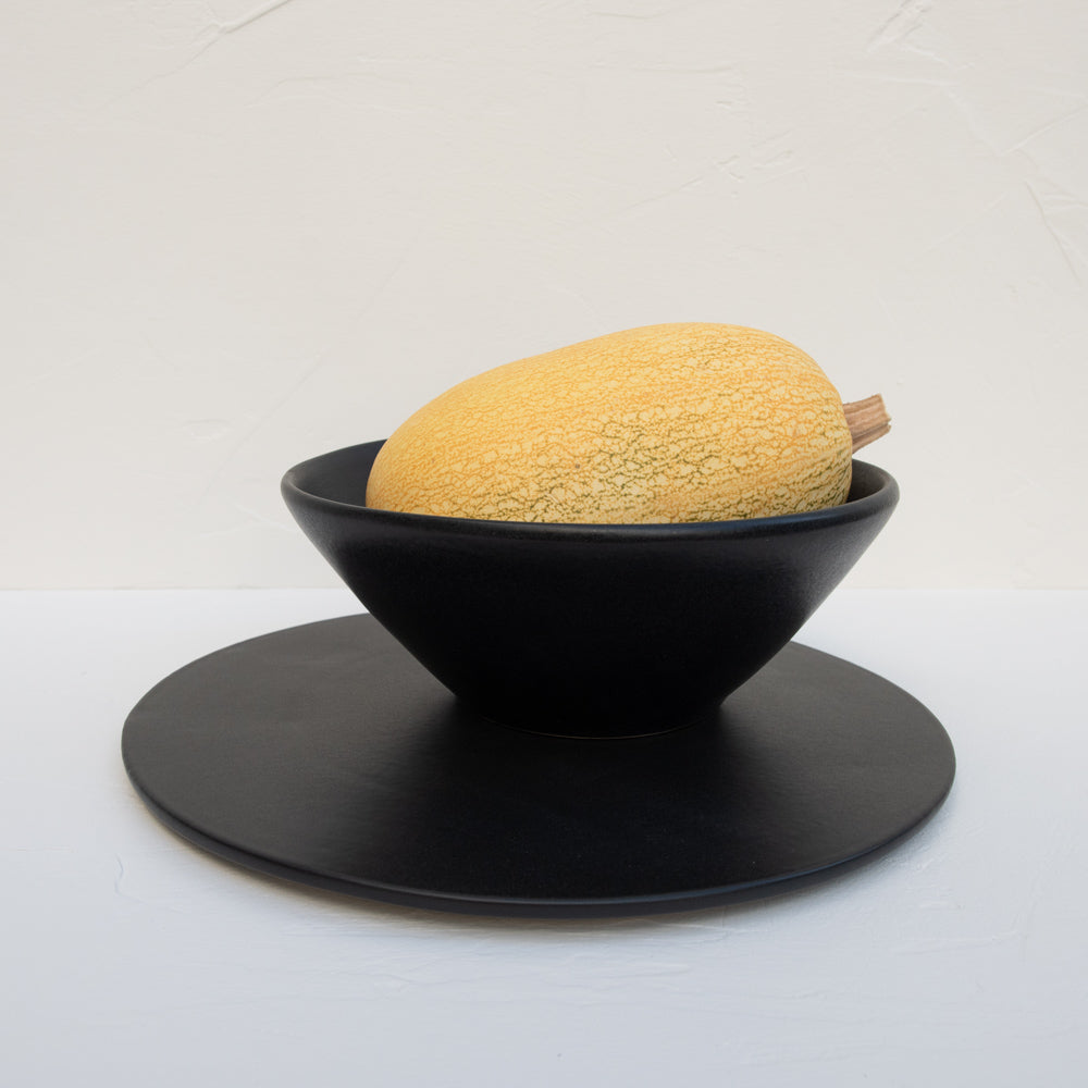 A matte-black stoneware serving platter and serving bowl (holding a large squash).