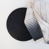 A matte black stoneware serving platter with a cotton Oaxaca hand towel.