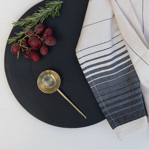 A stoneware serving platter with a brass tablespoon, Oaxaca hand towel and grapes/rosemary.