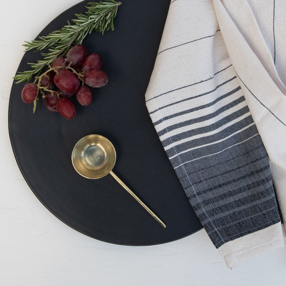 The Artesanal black stoneware serving platter paired with a Oaxaca hand towel and brass tablespoon.