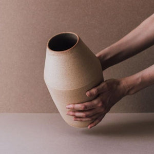 A terra-cotta ceramic vase being held in two hands.