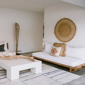 The living room of a modern beach house features white, minimalist furniture, palm accents, driftwood and handwoven wool pillows and a rug.