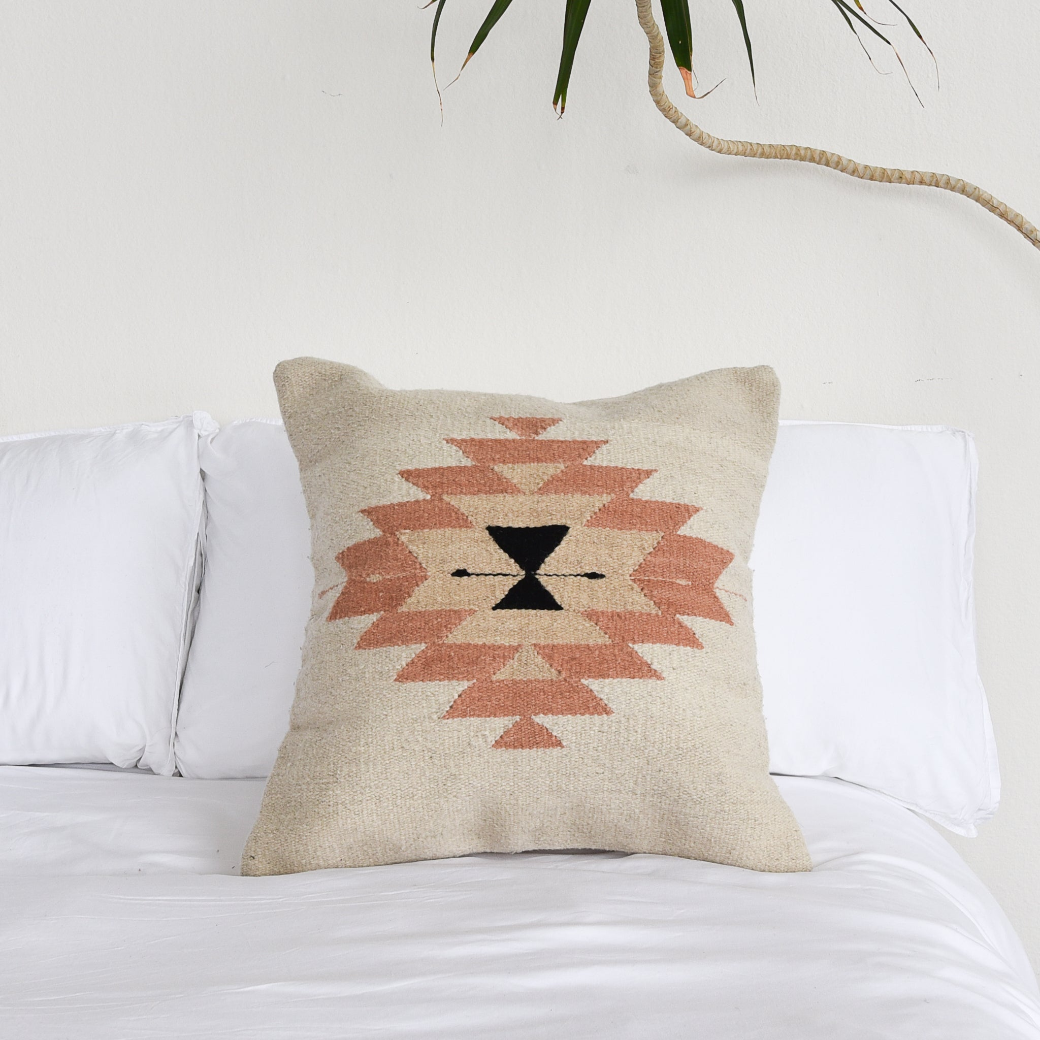 A wool throw pillow featuring Oaxaca Zapotec-inspired design on a white bed.