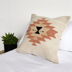 A wool throw pillow on a bed with white bedding.