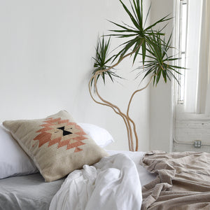 A handwoven wool throw pillow featuring Zapotec design on a cozy bed with a yucca plant alongside.