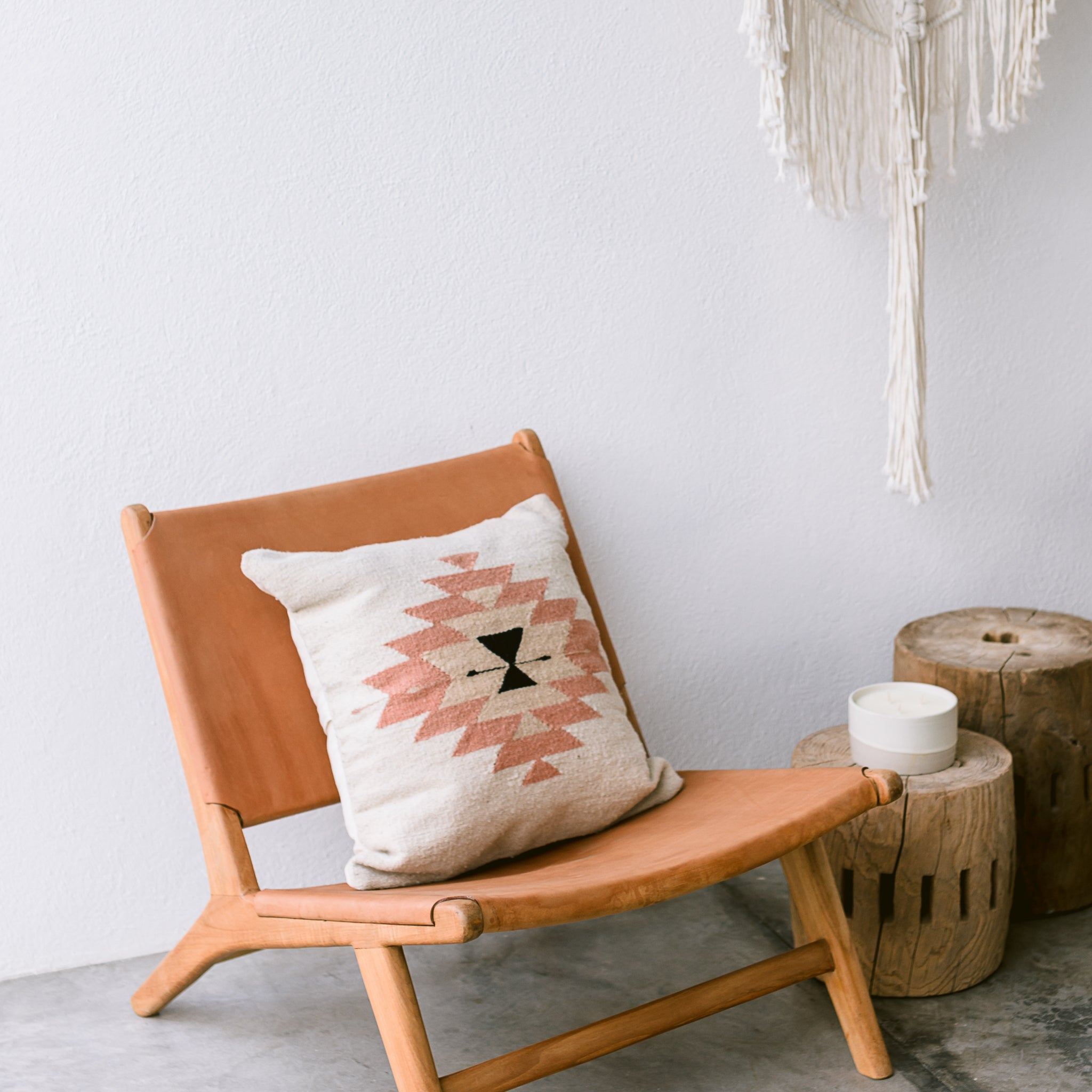A handwoven wool throw pillow featuring Zapotec designs and desert-inspired colors is arranged on a leather chair with small wood side tables.