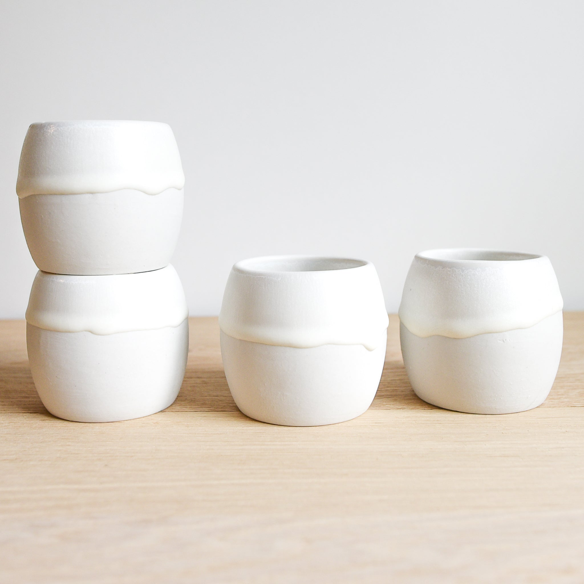 A set of four white glazed cups made of stoneware on a light wood table.