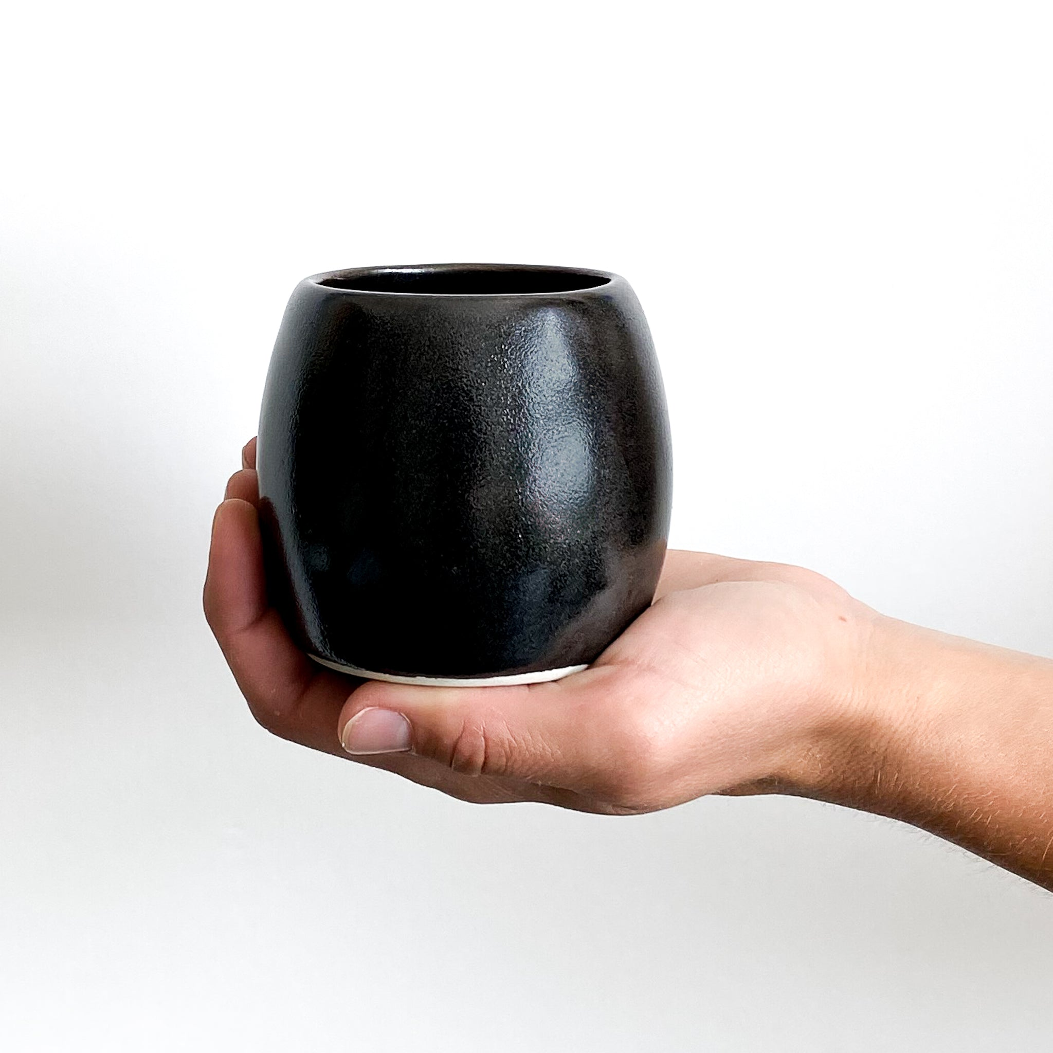 A hand holding a single black porcelain clay Yunomi cup against a white wall.
