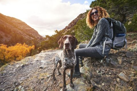 Woman on a hike sitting with her dog