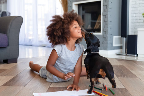 little girl laying on the floor playing with her dog