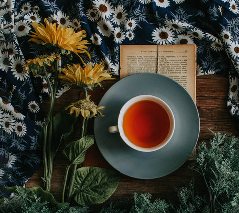 A cup of tea and a book on a table next to some flowers