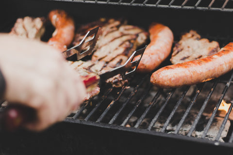 Person is barbecuing sausages and other meat on the BBQ grill
