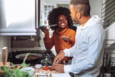 Heterosexual couple cooks in the kitchen and the woman is giving the man a taste while he chops tomatoes