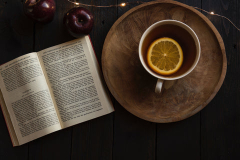Cup of tea with lemon and a book with two deep red apples
