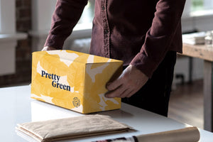 Person preparing to open Pretty Green yellow gift box to put sustainably wrapped Australian products in