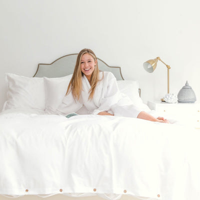 organic cotton luxury white bed sheets girl smiling comfortably