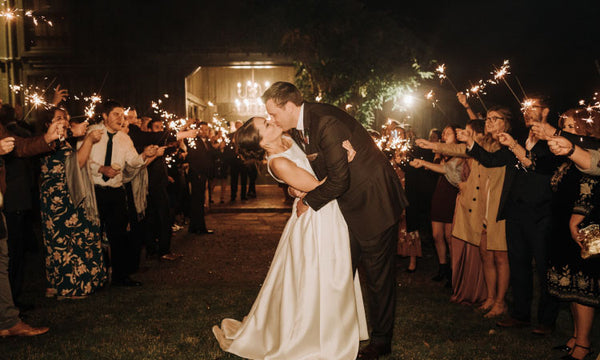 Bride and Groom Kissing Under Sparkler Display